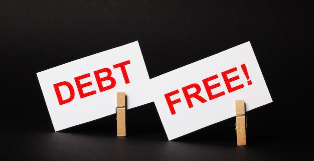 Na czarnym tle na drewnianych spinaczach do bielizny dwie białe puste kartki z napisem debt free