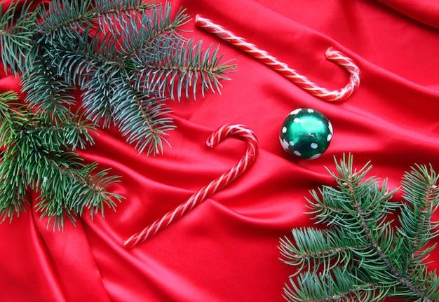 Na czerwonych jedwabnych gałęziach jodły, zielona świąteczna świeca i świąteczny czerwony karmel