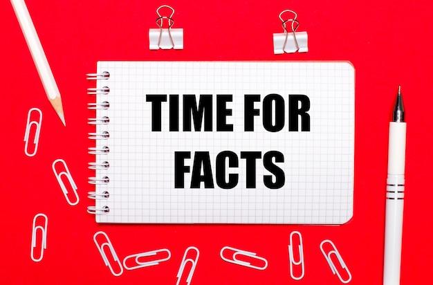 Na czerwonym tle biały długopis, białe spinacze, biały ołówek i notes z napisem czas na fakty. widok z góry