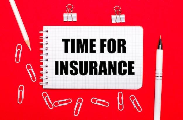 Na czerwonym tle biały długopis, białe spinacze, biały ołówek i notes z napisem czas na ubezpieczenie. widok z góry