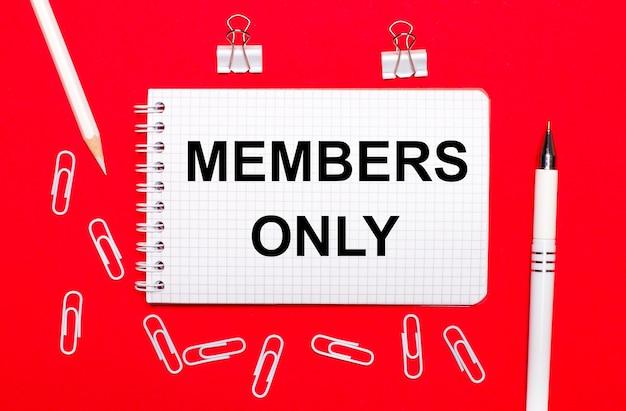 Na czerwonym tle biały długopis, białe spinacze, biały ołówek i notes z napisem members only. widok z góry