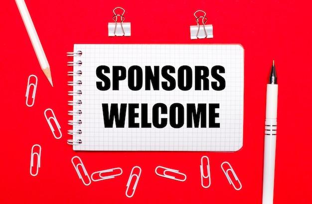Na czerwonym tle biały długopis, białe spinacze, biały ołówek i notes z napisem sponsorzy witamy. widok z góry