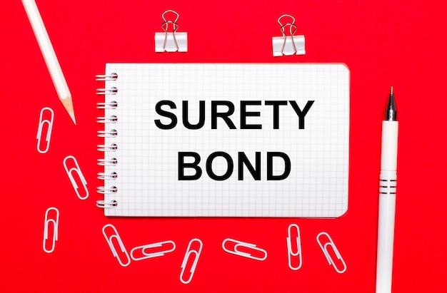 Na czerwonym tle biały długopis, białe spinacze, biały ołówek i notes z napisem surety bond. widok z góry