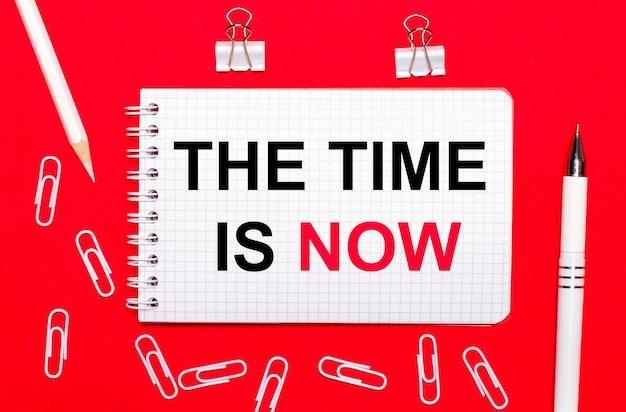 Na czerwonym tle biały długopis, białe spinacze, biały ołówek i notes z napisem the time is now. widok z góry