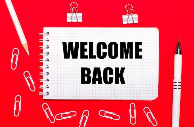 Na czerwonym tle biały długopis, białe spinacze, biały ołówek i notes z napisem witajcie z powrotem. widok z góry