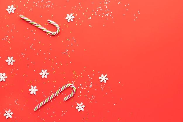 Na czerwonym tle płatki śniegu gwiazdki cukierki i karmelowy kij