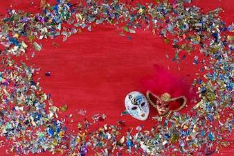 Na czerwonym tle są dwie karnawałowe maski i kolorowe konfetti wokół