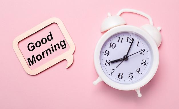 Na delikatnym różowym tle biały budzik i drewniana ramka z napisem good morning