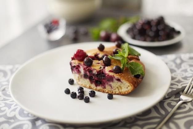 Na deser kawałek ciasta z jagodami, malinami i miętą