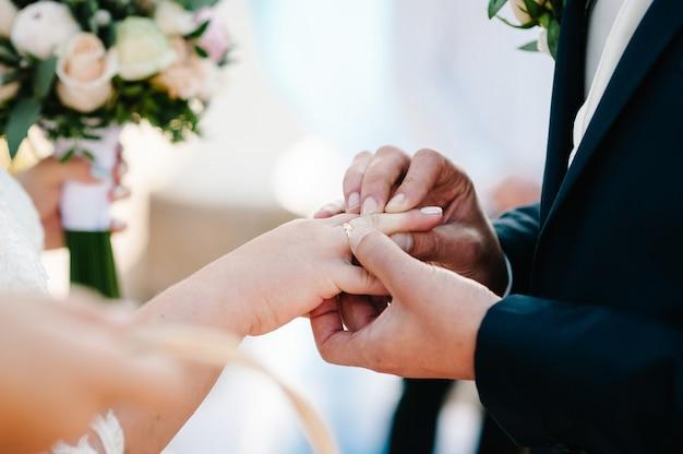 Na dłoni pana młodego na palcu panny młodej znajduje się złoty pierścionek zaręczynowy. dzień ślubu. ręce z obrączkami. ścieśniać.