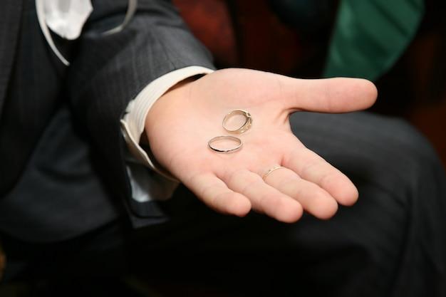 Na dłoni pana młodego znajdują się złote obrączki ślubne