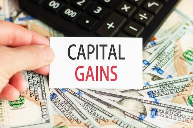 Na dłoni trzyma znak z napisem - zyski kapitałowe na ścianie banknotów i kalkulator na stole. koncepcja finansów i ekonomii.