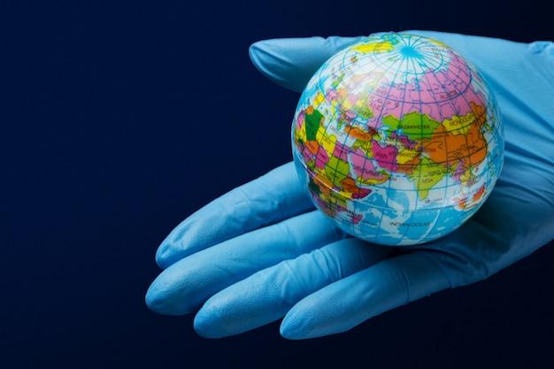 Na dłoni w rękawicy medycznej leży makieta planety ziemia, koncepcja globalnej pandemii koronawirusa