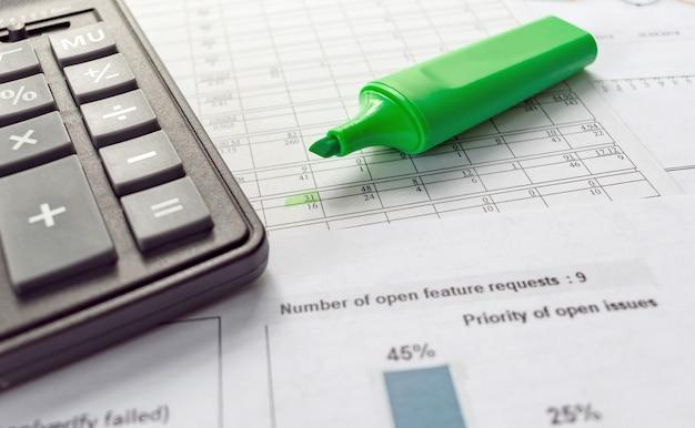 Na dokumencie finansowym zielony znacznik i kalkulator. koncepcja biznesowa i finansowa.