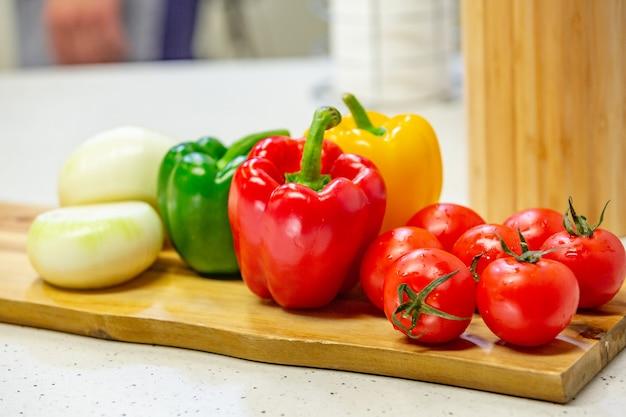 Na drewnianej desce są warzywa. pomidor, pieprz, apetyczna sałatka leżą na drewnianej desce