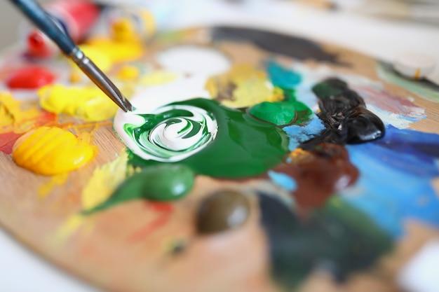 Na drewnianej palecie znajduje się wibrująca mieszanka farby do malowania profesjonalnego szkolenia malarskiego