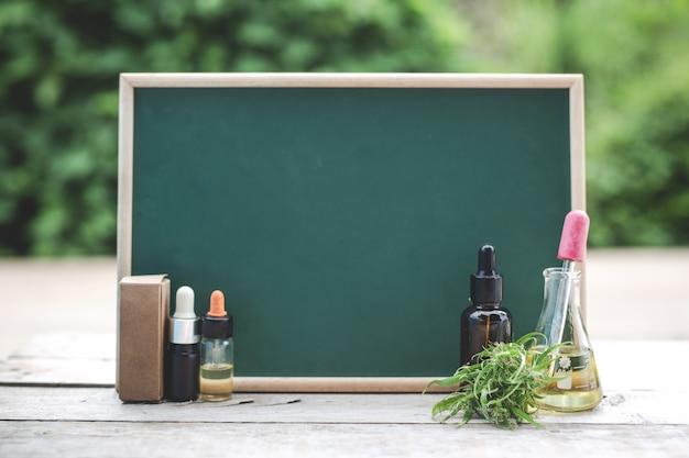 Na drewnianej podłodze jest olej konopny, liść konopi, a zielona tablica jest pusta, aby umieścić tekst.