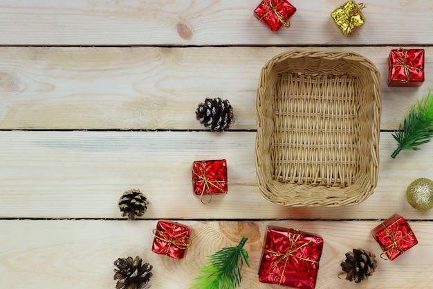 Na drewnianej podłodze umieszcza się wiklinowy kosz z dekoracjami świątecznymi na boże narodzenie i nowy rok.