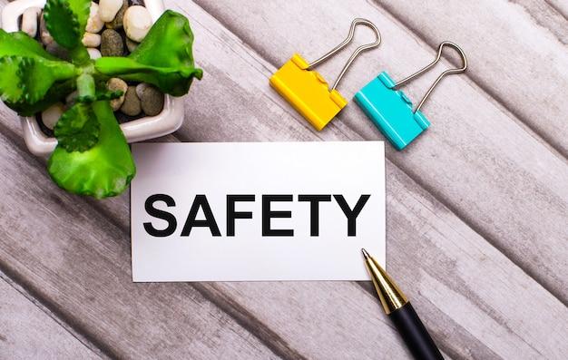 Na drewnianej powierzchni biała kartka z napisem bezpieczeństwo, żółto-zielone spinacze oraz roślina w doniczce