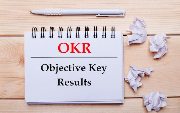 Na drewnianej powierzchni biały notatnik z napisem okr objective key results, biały długopis i zmięte białe kartki papieru