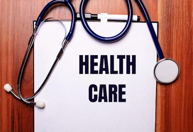 Na drewnianej powierzchni leży stetoskop i kartka z napisem zdrowie. leżał na płasko