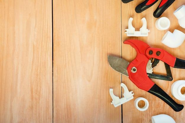 Na drewnianej przestrzeni znajdują się narzędzia do naprawy rur plastikowych.
