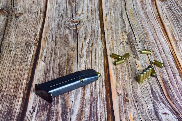 Na drewnianych brązowych deskach znajduje się magazynek do pistoletu i kilka rozrzuconych naboi z traumatycznego pistoletu.