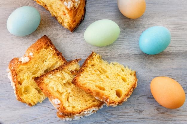 Na drewnianym blacie znajdują się plastry wielkanocnego ciasta i kolorowe jajka.