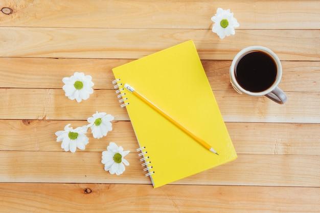 Na drewnianym notesie ołówek, kawa i kwiaty.