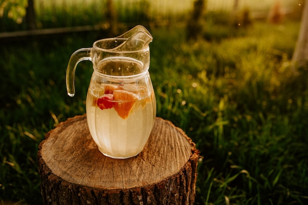 Na drewnianym pniu stoi szklany dzbanek z lemoniadą i owocami w środku. o zachodzie słońca na tle zielonej trawie. truskawki, pomarańcza, cytryna i mandarynka.