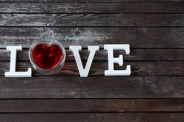 Na drewnianym stole ciemny kubek czerwonej herbaty i słowo miłość z białych drewnianych liter