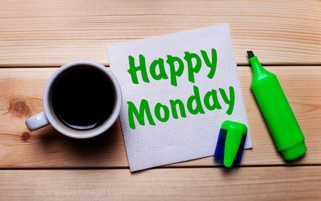 Na drewnianym stole filiżanka kawy, zielony marker i serwetka z napisem happy monday