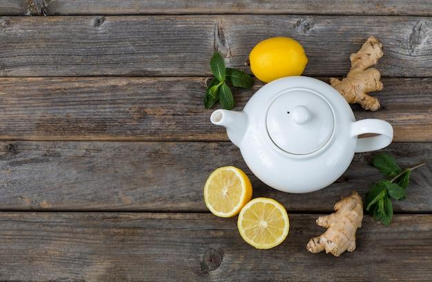 Na drewnianym stole jest biały czajniczek, cytryna, liście mięty i imbir. wolne miejsce na tekst