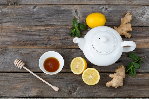Na drewnianym stole jest biały czajniczek, cytryna, miód, liście mięty i imbir. wolne miejsce na tekst