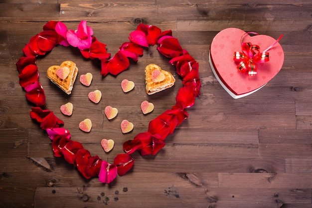 Na drewnianym stole jest pudełko w kształcie serca na prawo od płatków róż