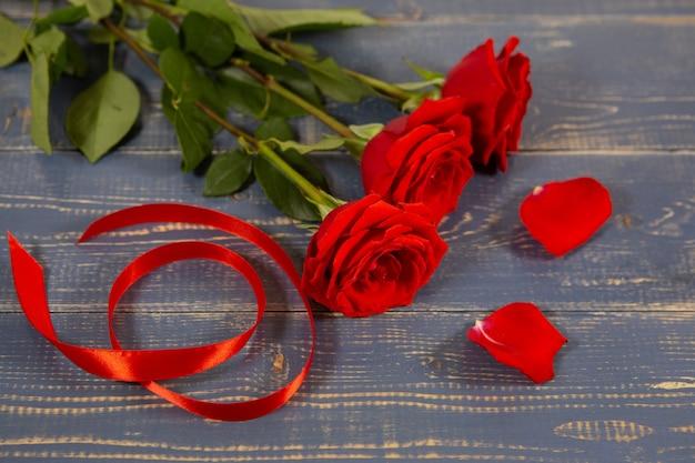 Na drewnianym stole leżą duże czerwone pąki róż ze wstążką prezentową i płatkami.