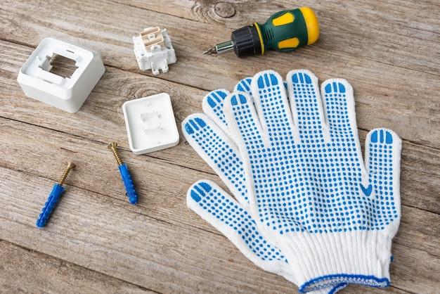 Na drewnianym stole leżą śrubokręt, włączniki światła i rękawiczki.