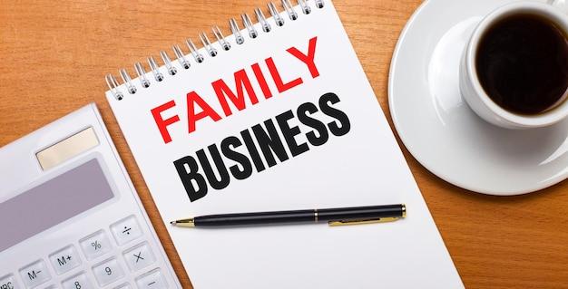 Na drewnianym stole leży biały kalkulator, biała filiżanka kawy, długopis i biały zeszyt z napisem rodzina biznes. pomysł na biznes