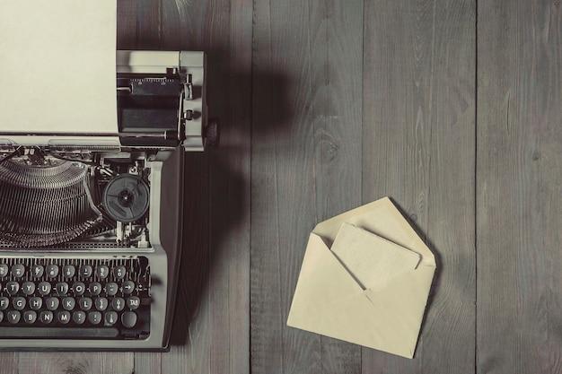 Na drewnianym stole leży stara maszyna do pisania z kartką papieru i otwartą kopertą z listem