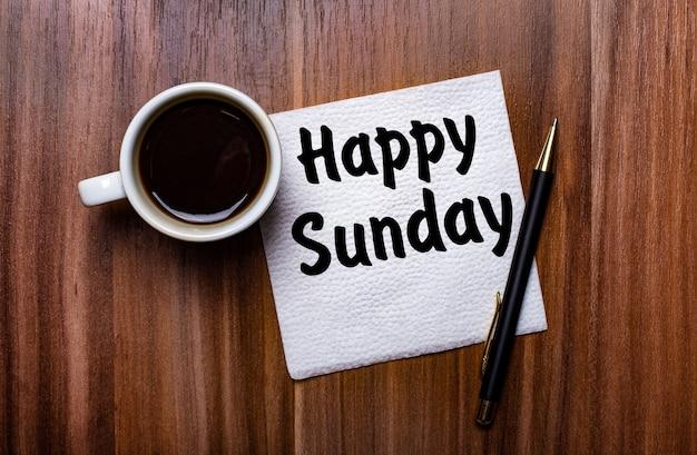 Na drewnianym stole obok białej filiżanki kawy i długopisu leży biała papierowa serwetka z napisem happy sunday