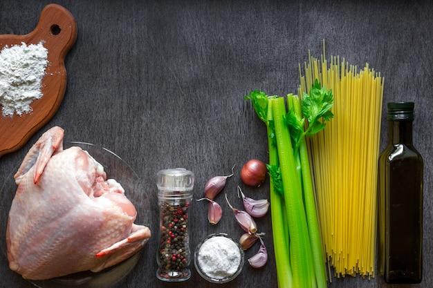 Na drewnianym stole piersi z kurczaka, olej, makaron spaghetti, seler, przyprawy i czosnek