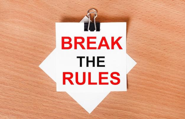 Na drewnianym stole pod czarnym spinaczem leży kartka białego papieru z napisem break the rules