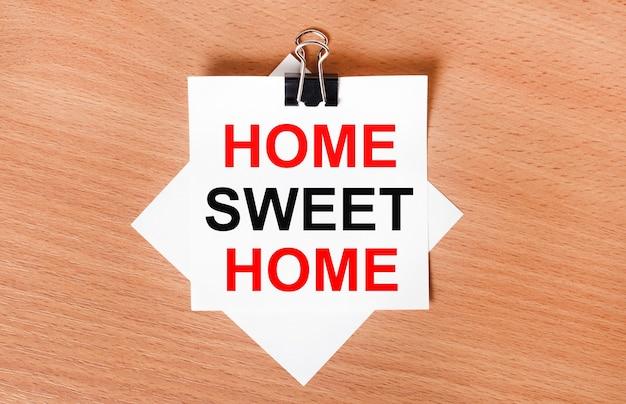 Na drewnianym stole pod czarnym spinaczem leży kartka białego papieru z napisem home sweet home