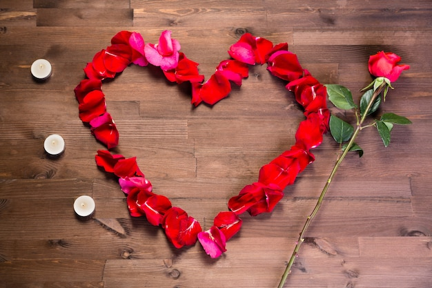 Na drewnianym stole serce z płatków róży, świeczki i jedna różowa róża