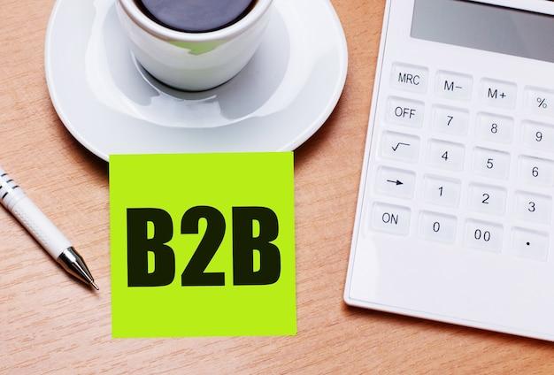 Na drewnianym stole stoi biała filiżanka kawy, długopis, biały kalkulator i zielona naklejka z napisem b2b. pomysł na biznes