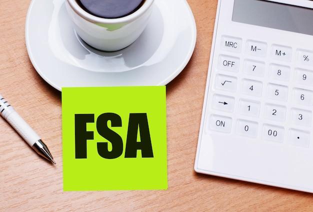 Na drewnianym stole stoi biała filiżanka kawy, długopis, biały kalkulator i zielona naklejka z napisem fsa flexible spending account. pomysł na biznes