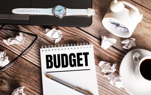 Na drewnianym stole stoi filiżanka kawy, zegar, szklanki i notes z napisem budget. pomysł na biznes