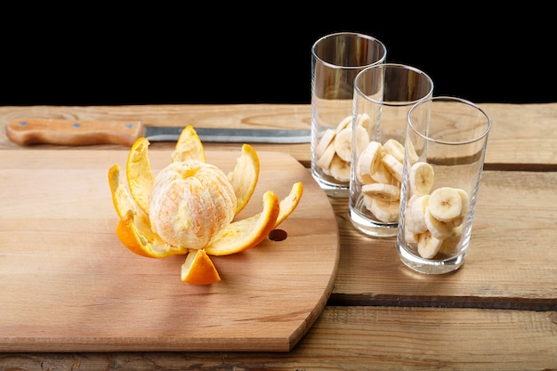 Na drewnianym stole stoi obrana pomarańcza i trzy szklanki z bananami na koktajl