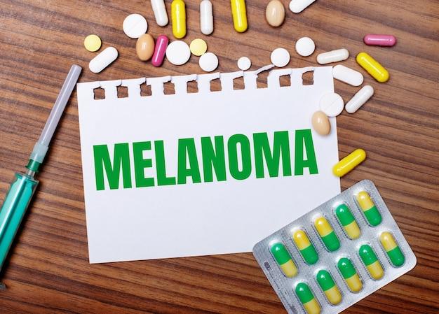Na drewnianym stole strzykawka, tabletki i kartka z napisem melanoma. pojęcie medyczne