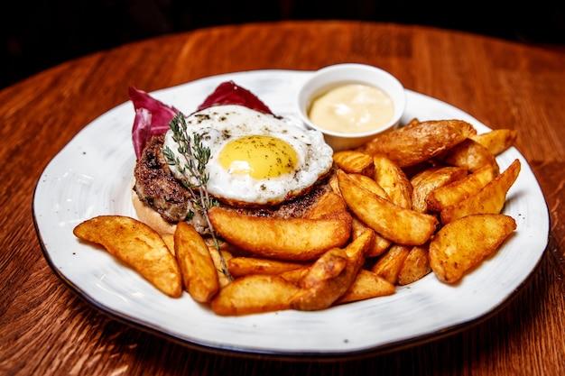 Na drewnianym stole talerz z obiadem: siekany stek z jajkiem, ziemniaki po wiejsku, sos. zbliżenie, restauracja.